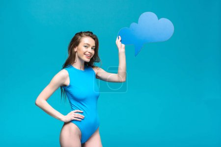 Photo for Pretty girl in swimsuit holding thought bubble isolated on blue - Royalty Free Image
