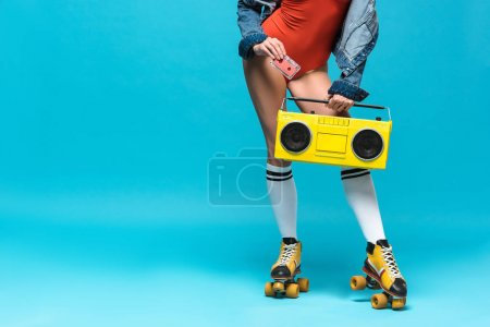 Photo for Cropped view of woman in swimsuit and roller skates holding boombox and cassette tape on blue - Royalty Free Image