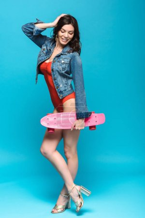 Photo for Full length view of pretty girl in swimsuit and denim jacket holding longboard on blue - Royalty Free Image