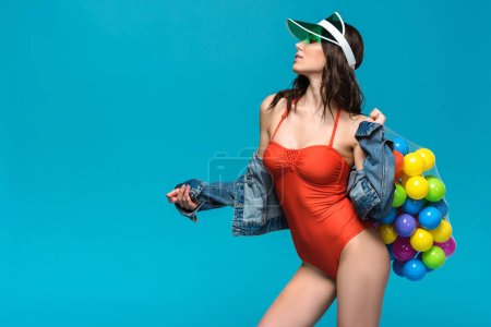 Photo for Gorgeous girl in swimsuit and denim jacket holding string bag with colorful balls isolated on blue - Royalty Free Image