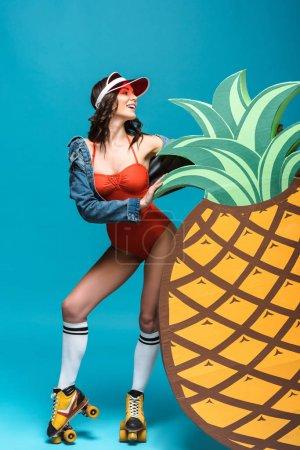 Photo pour Vue pleine longueur de femme dans le maillot de bain et les patins à roulettes restant près de l'ananas décoratif sur le bleu - image libre de droit