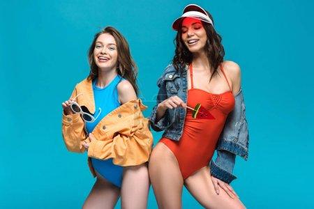 Foto de Dos chicas sonrientes en trajes de baño y chaquetas con piruleta de sandía aislada en azul - Imagen libre de derechos