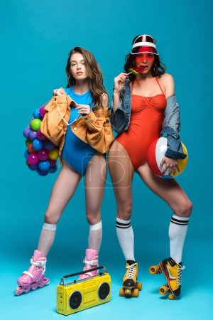 Photo for Full length view of two stylish girls in roller skates eating watermelon lollipop on blue - Royalty Free Image