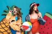 """Постер, картина, фотообои """"две девушки с пляжным мячом и леденец возле декоративного арбуза и ананаса изолированы на синем"""""""