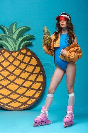 Photo pour Vue pleine longueur de fille dans le maillot de bain et les patins à roulettes retenant l'ananas sur le bleu - image libre de droit