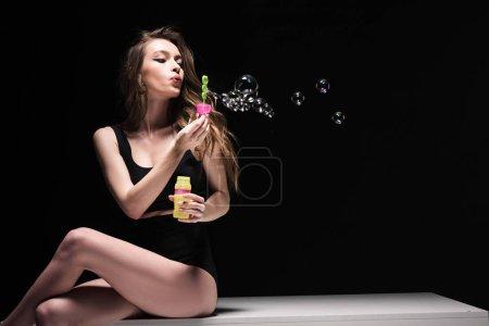 Photo pour Jolie jeune femme s'asseyant sur la table et soufflant des bulles de savon d'isolement sur le noir - image libre de droit