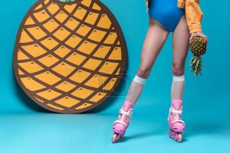 Photo pour Vue raccourcie de fille dans le maillot de bain et les patins à roulettes retenant l'ananas sur le bleu - image libre de droit