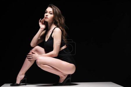 Photo pour Fille attirante dans des sous-vêtements et des talons s'asseyant sur la table d'isolement sur le noir - image libre de droit