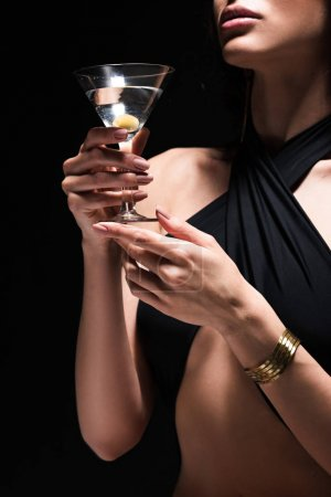 Photo for Cropped view of sexy woman holding glass of martini with olive isolated on black - Royalty Free Image