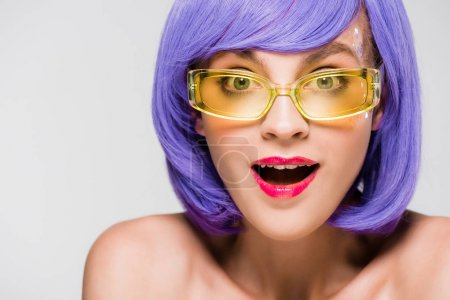 Photo for Excited girl in purple wig and trendy sunglasses isolated on grey - Royalty Free Image
