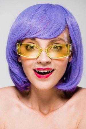 Foto de Beautiful surprised girl in purple wig and sunglasses isolated on grey - Imagen libre de derechos