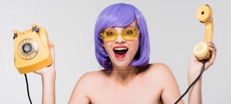 Photo pour Femme nue excitée dans la perruque pourpre retenant le téléphone rétro, d'isolement sur le gris - image libre de droit