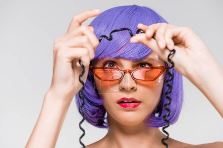 Photo pour Woman in purple wig looking at cord of vintage telephone, isolated on grey - image libre de droit