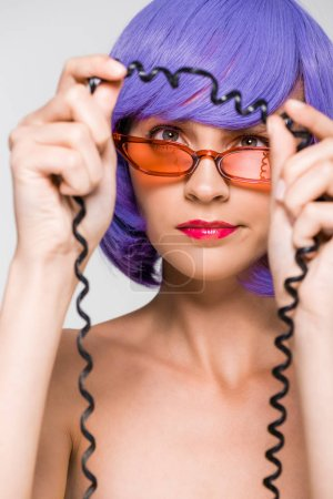 Foto de Woman in purple wig looking at cord of vintage telephone, isolated on grey - Imagen libre de derechos