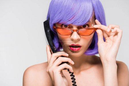 Photo pour Femme choquée dans la perruque pourpre retenant le téléphone rétro, d'isolement sur le gris - image libre de droit