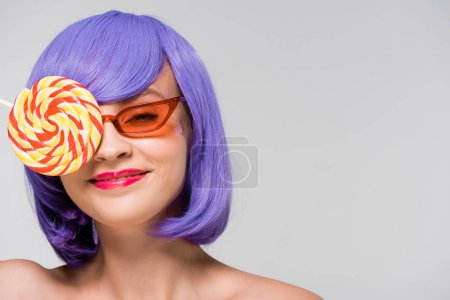 Photo pour Fille de sourire dans la perruque et les lunettes de soleil pourpres retenant la sucette douce, d'isolement sur le gris - image libre de droit