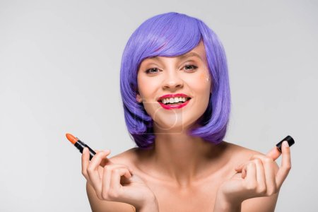Photo for Beautiful girl in purple wig holding lipstick isolated on grey - Royalty Free Image