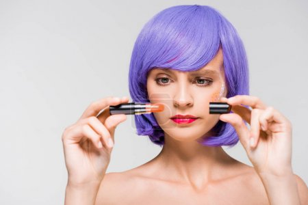 Photo pour Confused girl in purple wig holding lipstick isolated on grey - image libre de droit