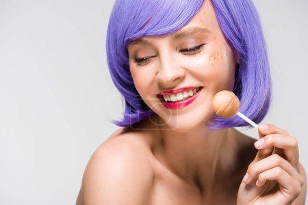 Photo pour Fille nue de sourire dans la perruque pourpre retenant la sucette douce, d'isolement sur le gris - image libre de droit