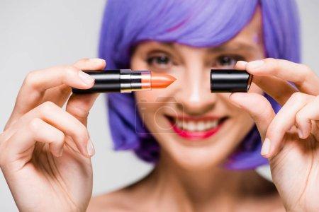 Photo pour Foyer sélectif de fille de sourire dans le rouge à lèvres de fixation de perruque pourpre d'isolement sur le gris - image libre de droit