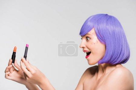 Photo pour Jeune femme excitée dans la perruque pourpre retenant des rouges à lèvres d'isolement sur le gris - image libre de droit
