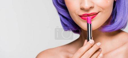 Photo pour Vue recadrée de fille dans le rouge à lèvres de fixation de perruque pourpre d'isolement sur le gris - image libre de droit
