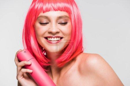 Photo pour Fille nue heureuse dans le jet rose de fixation de cheveux de perruque, d'isolement sur le gris - image libre de droit