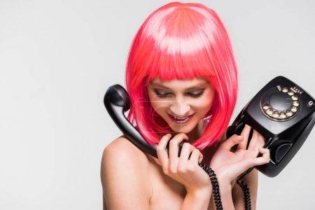 Foto de Hermosa mujer sonriente en peluca rosa hablando en el teléfono vintage, aislado en gris - Imagen libre de derechos