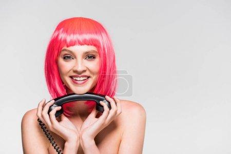 Foto de Chica bastante sonriente en la peluca rosa sosteniendo el teléfono vintage, aislado en gris - Imagen libre de derechos