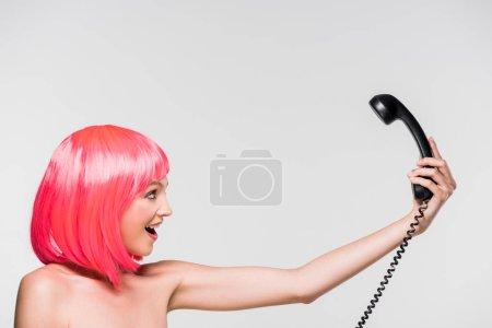 Photo pour Belle femme dans la perruque rose regardant le téléphone rétro, d'isolement sur le gris - image libre de droit