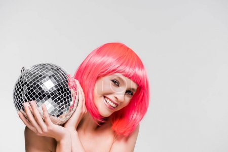 Photo for Smiling girl in pink wig holding disco ball, isolated on grey - Royalty Free Image