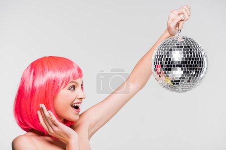 Photo pour Fille excitée dans la boule rose de fixation de perruque de disco, d'isolement sur le gris - image libre de droit