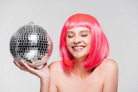 Photo pour Fille heureuse attirante dans la boule rose de fixation de perruque de disco, d'isolement sur le gris - image libre de droit