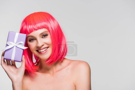 Photo for Attractive girl in pink wig holding present, isolated on grey - Royalty Free Image