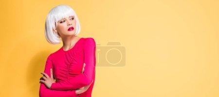 Photo pour Jolie fille en perruque blanche avec les bras croisés isolés sur jaune - image libre de droit