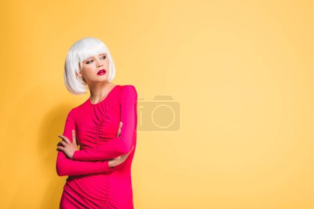 Photo pour Jolie fille en perruque blanche avec les bras croisés isolés sur le jaune - image libre de droit