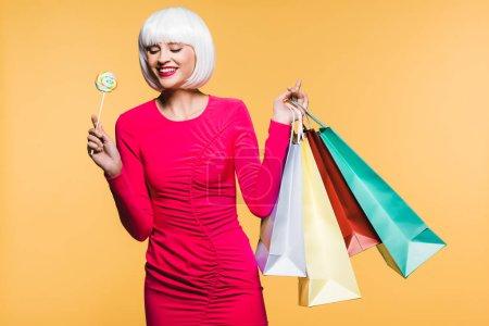Photo pour Fille de sourire dans la perruque blanche avec des sacs à provisions et sucette, d'isolement sur le jaune - image libre de droit