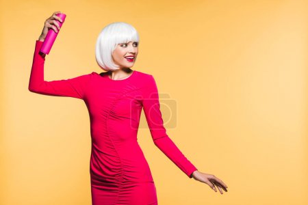Photo pour Fille élégante dans le jet blanc de cheveux de fixation de perruque, d'isolement sur le jaune - image libre de droit