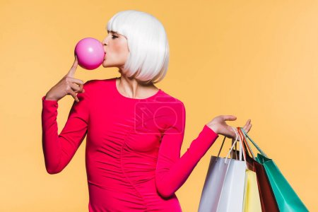 Foto de Cheerful girl in white wig with shopping bags and bubble gum, isolated on yellow - Imagen libre de derechos