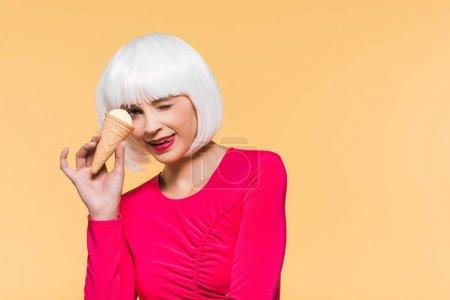 Foto de Beautiful winking girl in white wig eating ice cream, isolated on yellow - Imagen libre de derechos