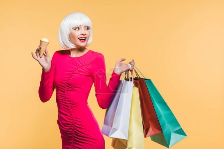 Foto de Cheerful girl in white wig with shopping bags and ice cream, isolated on yellow - Imagen libre de derechos