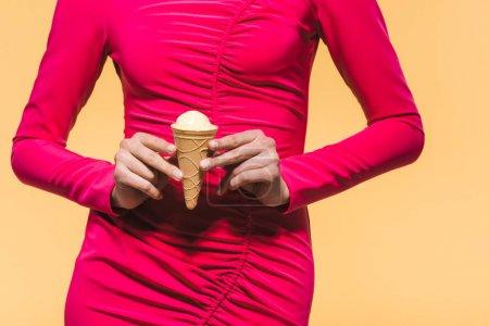 Foto de Partial view of stylish girl holding ice cream, isolated on yellow - Imagen libre de derechos