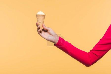 Foto de Partial view of woman holding ice cream in hand, isolated on yellow - Imagen libre de derechos