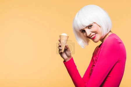 Foto de Smiling girl in white wig eating ice cream, isolated on yellow - Imagen libre de derechos