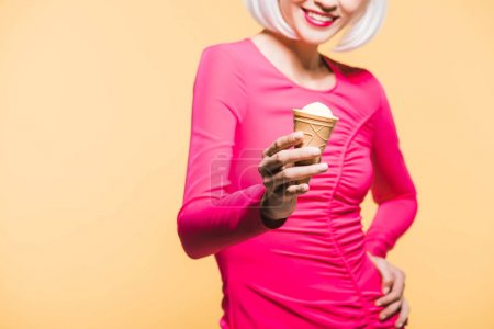 Foto de Cropped view of smiling girl in white wig eating ice cream, isolated on yellow - Imagen libre de derechos