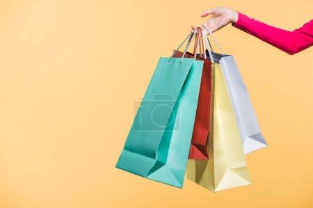 Photo pour Vue recadrée de femme avec des sacs à provisions, d'isolement sur le jaune - image libre de droit