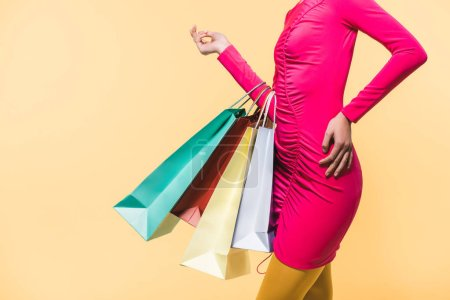 Foto de Cropped view of stylish woman with shopping bags, isolated on yellow - Imagen libre de derechos