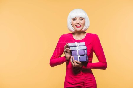 Foto de Beautiful smiling girl in white wig holding gift boxes, isolated on yellow - Imagen libre de derechos