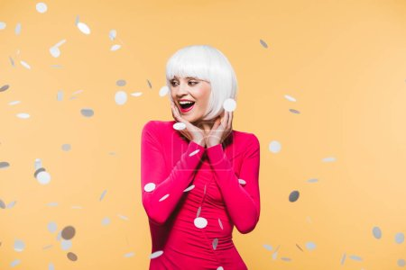 Photo for Beautiful surprised woman in red dress and white wig posing with holiday confetti, isolated on yellow - Royalty Free Image