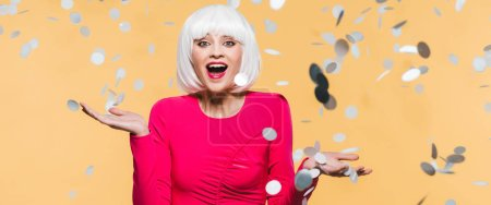 Photo pour Excited surprised girl in red dress and white wig posing with holiday confetti, isolated on yellow - image libre de droit